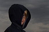 Boy with face partially obscured by jacket hood, looking at camera