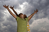 Boy and girl with arms raised, heads back looking up at cloudy sky