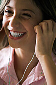 Female listening to music with earphones, smiling
