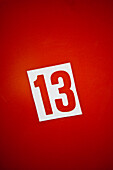 Number thirteen against red background