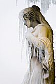 Statue of female figure, face obscured by icicles
