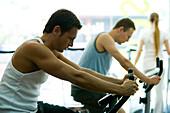 Men on exercise bikes in gym