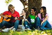 Young man sitting with friends under tree, playing guitar
