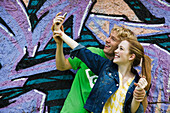 Young couple photographing themselves with cell phone