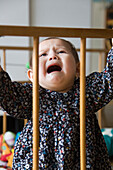 Baby girl crying in crib