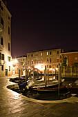 Italy, Venice, gondolas docked along canal at night