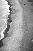 Person standing on beach, aerial view, b&w