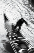 Person rowing gondola, high angle view, b&w