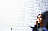 Woman talking on cell phone leaning against tiled wall