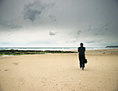 Person walking on beach, rear view