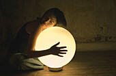 Woman holding glowing orb lamp