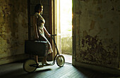 Woman standing by doorway on scooter, holding suitcase