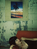 Woman lying on sofa with eyes closed, smiling, color photo on wall in background