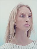 Teenage girl with windblown hair, looking away, portrait