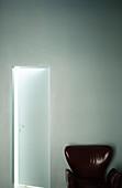Empty armchair next to open door