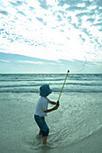 Boy throwing out fishing line on beach, rear view