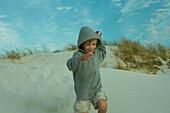 Boy running down dune