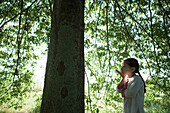 Girl standing under tree, blowing kiss, side view