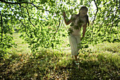 Girl walking under branches, looking up, full length