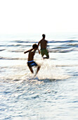 Man and boy playing in waves at beach