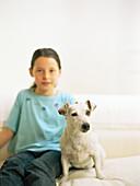Girl sitting on sofa with dog