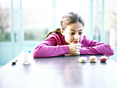 Girl sitting with head on table, looking at three cookies