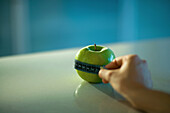 Woman holding measuring tape around apple, cropped view of hand