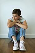 Teenage girl sitting on hardwood floor, hugging knees, looking away from camera