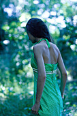 Rear view of a young woman walking through forest, wearing sundress, selective focus