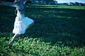 Woman wearing skirt, jumping in field with arms out, blurred motion