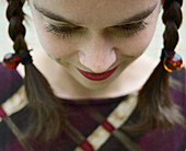 Young woman with pigtails looking down, close-up