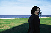 Woman looking over shoulder in seaside park