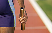 Athlete holding relay baton, partial view, close-up