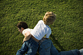 Two boys wrestling on grass, high angle view