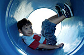 Boy sitting in playground tunnel with legs up, looking at camera, full length