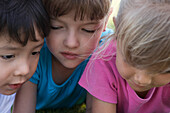 Three children with heads close together, cropped
