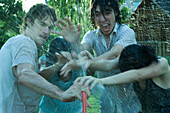 Young friends having water fight with garden hose