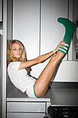 Young Woman in Underwear and Knee Socks Stretching Legs on Kitchen Counter