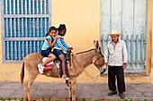 Photo opportunity, Happy children sitting on a donkey, Trinidad, Sancti Spiritus, Cuba, Caribbean