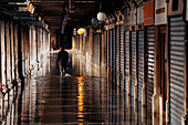 Lonely man goes along alley, Reflection, flood water, Aqua Alta, arcades, Piazza San Marco, Venice, Italy