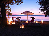 Deckchairs and umbrella at lake Chiemsee in sunset, Feldwies, Uebersee, Chiemgau, Bavaria, Germany