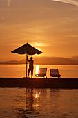 Sunrise at Krautinsel, man opening sunshade, Lake Chiemsee, Chiemgau, Bavaria, Germany