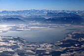 Aerial shot of northern lake Chiemsee in winter, Chiemgau Alps in background, Bavaria, Germany