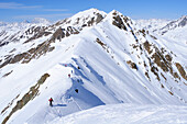 Group of people backcountry skiing, going down a ridge, Villgraten range in background, Kreuzspitze, Villgraten range, Hohe Tauern range, East Tyrol, Austria, Europe