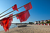 Fishing boat and red flags on the beach, Bansin seaside resort, Usedom island, Baltic Sea, Mecklenburg-West Pomerania, Germany