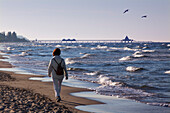 Woman walking along the beach towards the pier, Heringsdorf seaside resort, Usedom island, Baltic Sea, Mecklenburg-West Pomerania, Germany