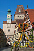 Fountain decorated with Easter eggs, Markus Tower with the Röder Arch, Rothenburg ob der Tauber, Franconia, Bavaria, Germany