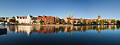 View over river Trave to old town with warehouse buildings, St. Mary' s church and church of St Peter, Hanseatic City of Luebeck, Schleswig Holstein, Germany
