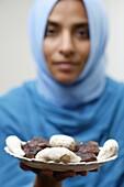 France, Paris, Muslim woman offering Ramadan pastries