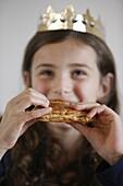 France, Girl eating Galette des rois, French pastry eaten on Epiphany